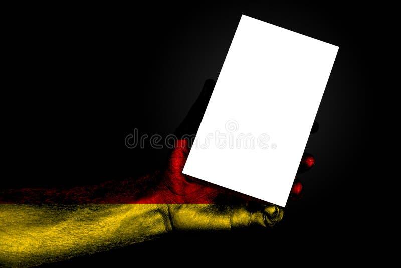 Το χέρι με τη χρωματισμένη σημαία Γερμανία που κρατά ένα μεγάλο άσπρο φύλλο με το διάστημα για μια επιγραφή, χλευάζει επάνω στοκ εικόνα με δικαίωμα ελεύθερης χρήσης