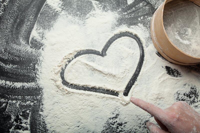 Το χέρι μιας γυναίκας επισύρει την προσοχή μια καρδιά στο αλεύρι, μια ρομαντική διάθεση στοκ εικόνες