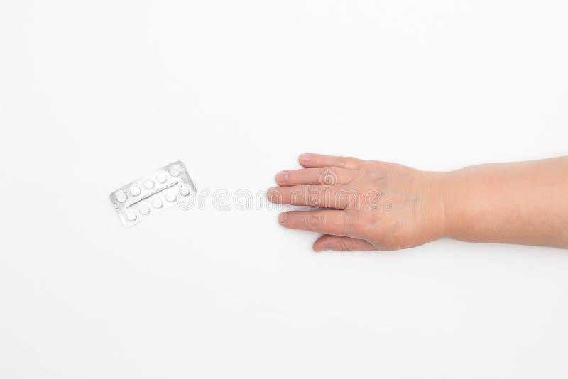 Το χέρι μιας ηλικιωμένης γυναίκας φθάνει για τα χάπια σε ένα άσπρο υπόβαθρο, η έννοια των χαπιών ψευδοφαρμάκου, υγεία, κινηματογρ στοκ εικόνες