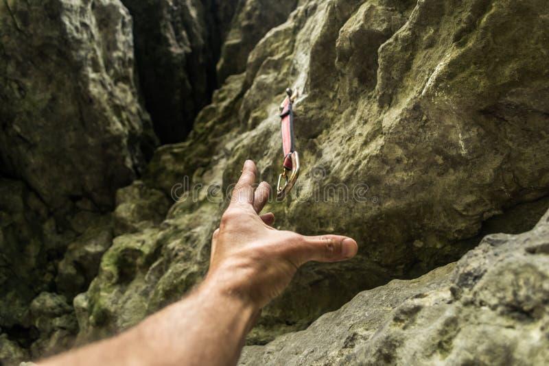 Το χέρι ορειβατών φθάνει στο carbine στοκ εικόνες