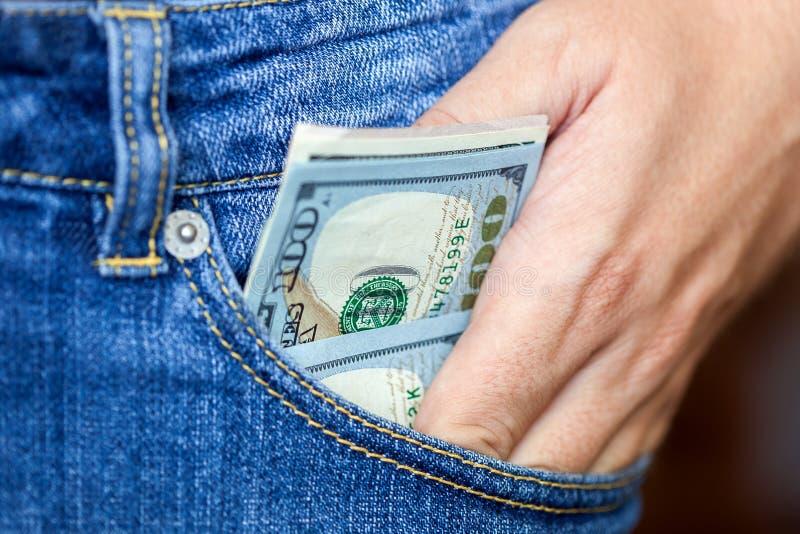 Το χέρι παίρνει τα δολάρια από μια τσέπη στοκ φωτογραφίες