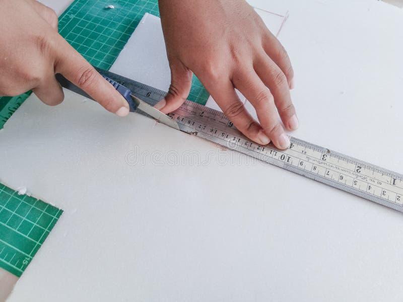 Το χέρι παιδιών κόβει το έγγραφο αφρού με ένα μαχαίρι κοπτών στοκ φωτογραφία