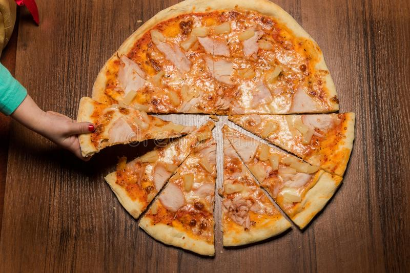 Το χέρι παιδιών παίρνει το ένα κομμάτι της πίτσας με τα κομμάτια prosciutto στοκ εικόνες