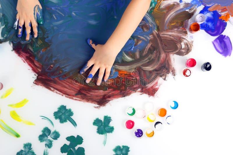 Το χέρι παιδιών χρωματίζει μια εικόνα με τα χρώματα στο άσπρο υπόβαθρο στοκ εικόνα με δικαίωμα ελεύθερης χρήσης