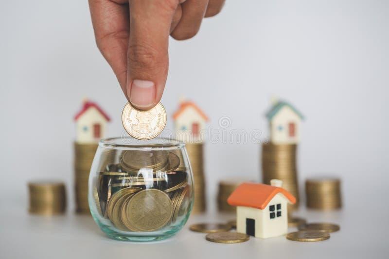 Το χέρι που βάζει το σωρό νομισμάτων χρημάτων, αγοράζει ένα σπίτι, κίνδυνος, δείχνει την αύξηση του σπιτιού και της χρηματοδότηση στοκ φωτογραφίες
