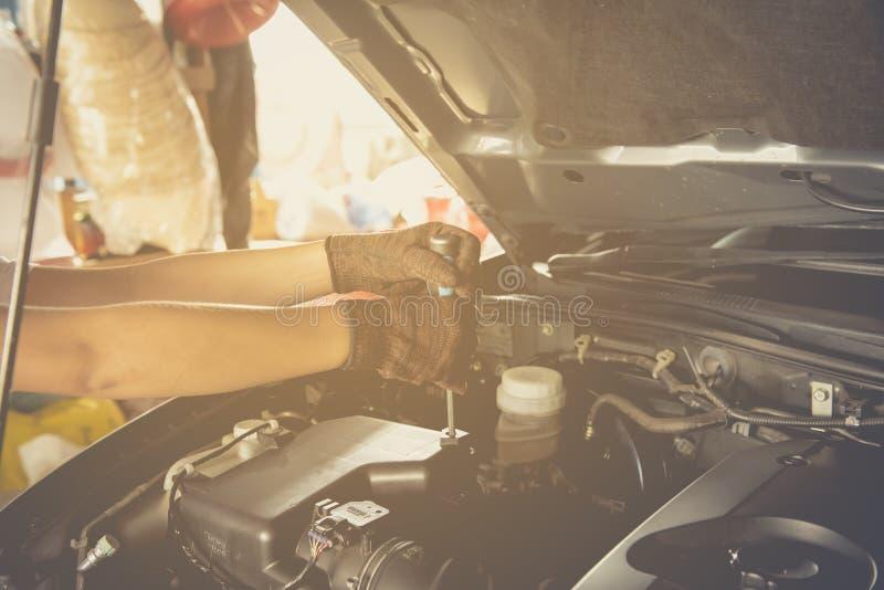 Το χέρι που κρατά ένα γαλλικό κλειδί με ένα αυτοκίνητο επισκευάζει, επαγγελματικός αυτόματος μηχανικός στοκ φωτογραφία