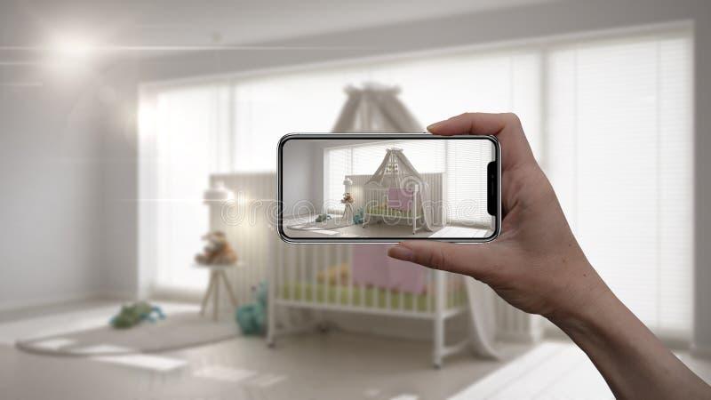 Το χέρι που κρατά το έξυπνο τηλέφωνο, εφαρμογή του AR, μιμείται τα έπιπλα και τα εσωτερικά προϊόντα σχεδίου στο πραγματικό σπίτι, στοκ εικόνες