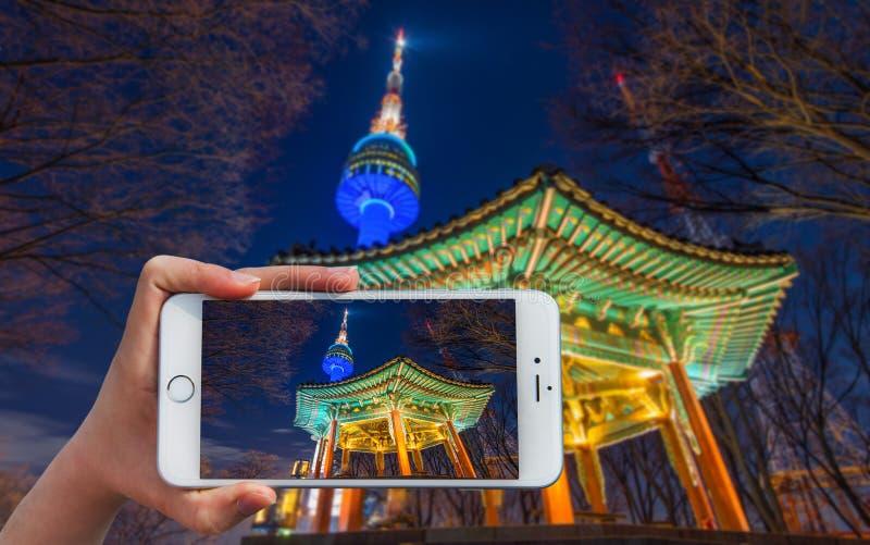 Το χέρι που κρατά το έξυπνο τηλέφωνο παίρνει μια φωτογραφία στον πύργο της Σεούλ στοκ εικόνες