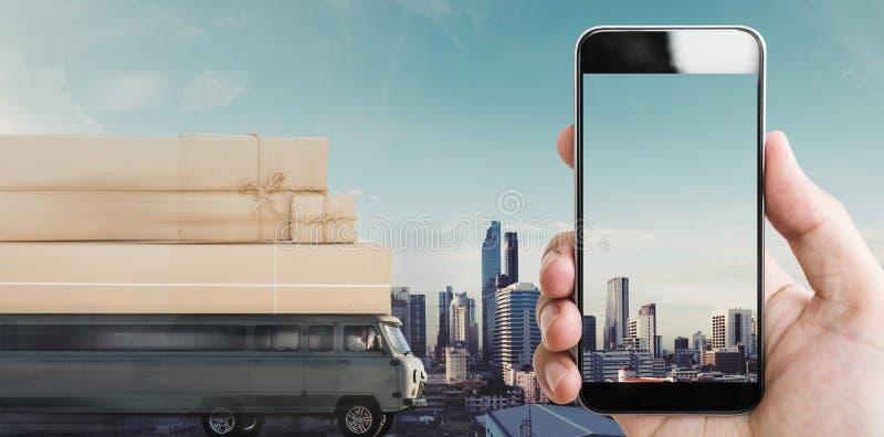 Το χέρι που κρατούν την κινητή έξυπνη τηλεφωνική κενή οθόνη, και το φορτηγό παράδοσης με τα κιβώτια δεμάτων στη στέγη που οδηγεί  στοκ εικόνα