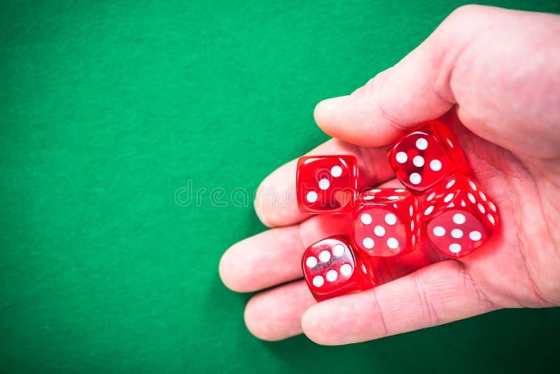 Το χέρι που ρίχνει το κόκκινο χωρίζει σε τετράγωνα, καλή έννοια τύχης στοκ εικόνες
