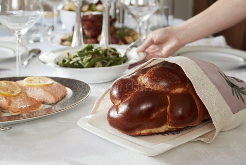 Το χέρι που τοποθετεί το πιάτο στον πίνακα που τίθεται για εβραϊκό Shabbat, κλείνει επάνω στοκ εικόνες με δικαίωμα ελεύθερης χρήσης