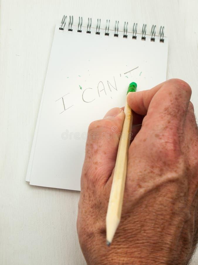 Το χέρι σβήνει το γράμμα Τ από τη λέξη δεν μπορεί στοκ εικόνες