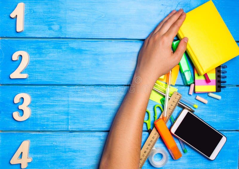 το χέρι σχολικών σπουδαστών καθαρίζει μακριά τις σχολικές προμήθειες στο μπλε ξύλινο επιτραπέζιο υπόβαθρο ο σπουδαστής προτιμά να στοκ εικόνες