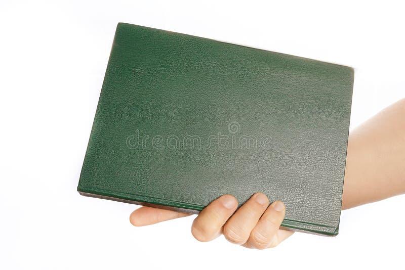 Το χέρι της γυναίκας κρατά μια πράσινη βίβλο στοκ εικόνα