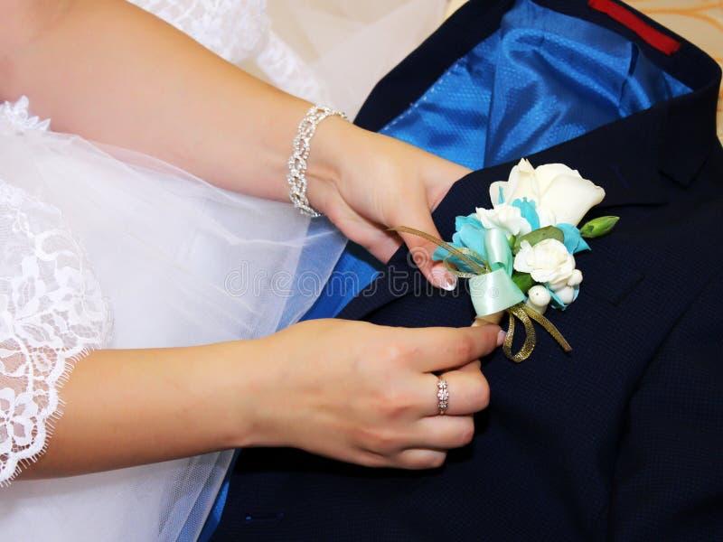 Το χέρι της νύφης βάζει σε ένα λουλούδι μπουτονιέρων στο σακάκι του νεόνυμφου Τόσο κοντά στοκ φωτογραφία