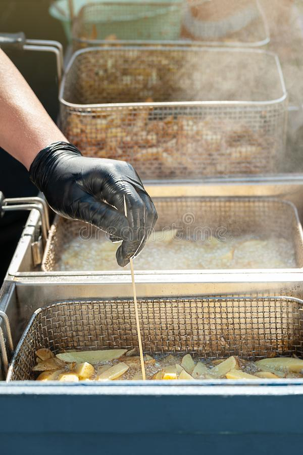 Το χέρι του αρχιμάγειρα ελέγχει την ποιότητα των τσιγαρισμένων πατατών Τηγανιτές πατάτες που τηγανίζονται στο βράζοντας πετρέλαιο στοκ φωτογραφία