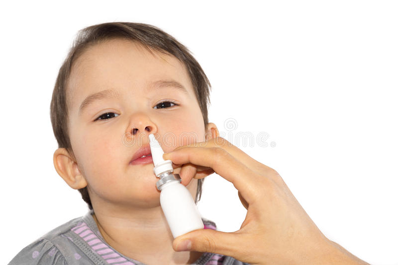 Το χέρι του γονέα ενός άρρωστου μικρού κοριτσιού εφαρμόζει έναν ρινικό ψεκασμό που απομονώνεται στοκ εικόνες