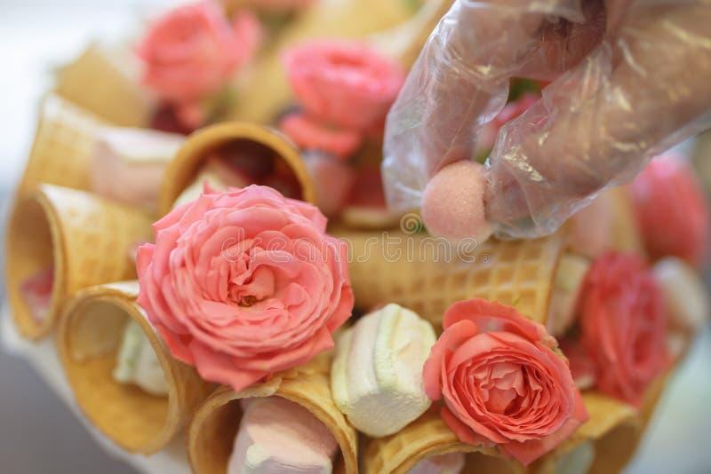Το χέρι του ζαχαροπλάστη σε ένα γάντι πολυαιθυλενίου διακοσμεί την ανθοδέσμη των τριαντάφυλλων και των γλυκών στοκ φωτογραφίες με δικαίωμα ελεύθερης χρήσης