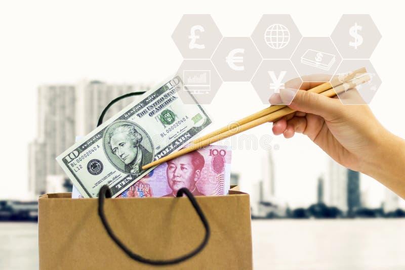 Το χέρι του θηλυκού κρατά chopsticks, τα οποία στερεώνουν yuan και το τραπεζογραμμάτιο δολαρίων από την τσάντα εγγράφου Η έννοια  στοκ εικόνα