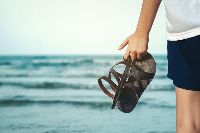 Το χέρι του κοριτσιού που κρατά τις παντόφλες και που έχει τη θάλασσα ως υπόβαθρο στοκ εικόνα με δικαίωμα ελεύθερης χρήσης