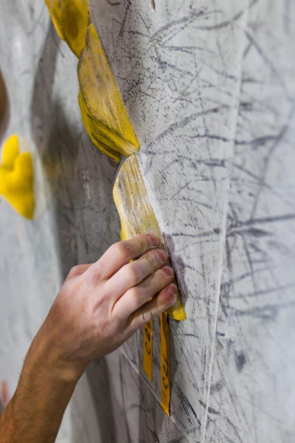 Το χέρι του λευκού κρατά στον τοίχο αναρρίχησης στοκ φωτογραφίες