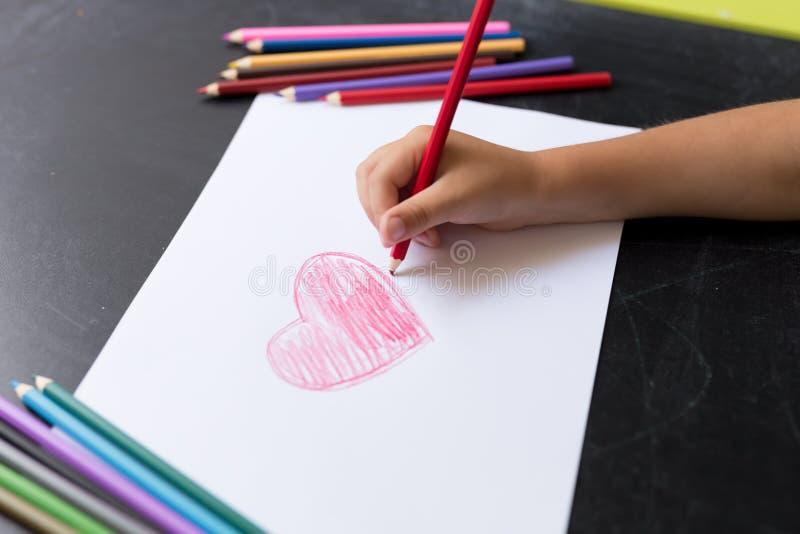 Το χέρι του παιδιού με το μολύβι επισύρει την προσοχή την καρδιά στη Λευκή Βίβλο Έννοια ημέρας μητέρων ` s Εορτασμός Χέρι - γίνον στοκ εικόνες