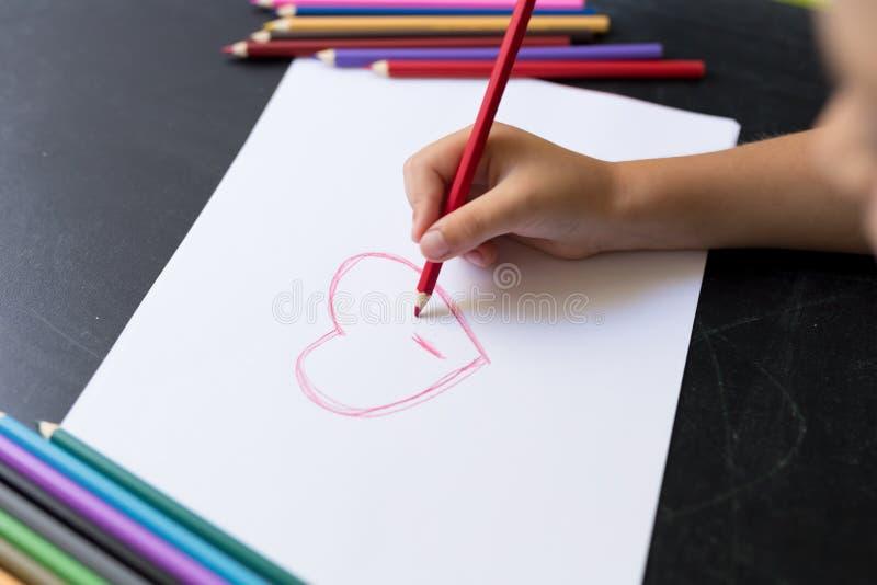 Το χέρι του παιδιού με το μολύβι επισύρει την προσοχή την καρδιά στη Λευκή Βίβλο Έννοια ημέρας μητέρων ` s Εορτασμός Χέρι - γίνον στοκ φωτογραφίες
