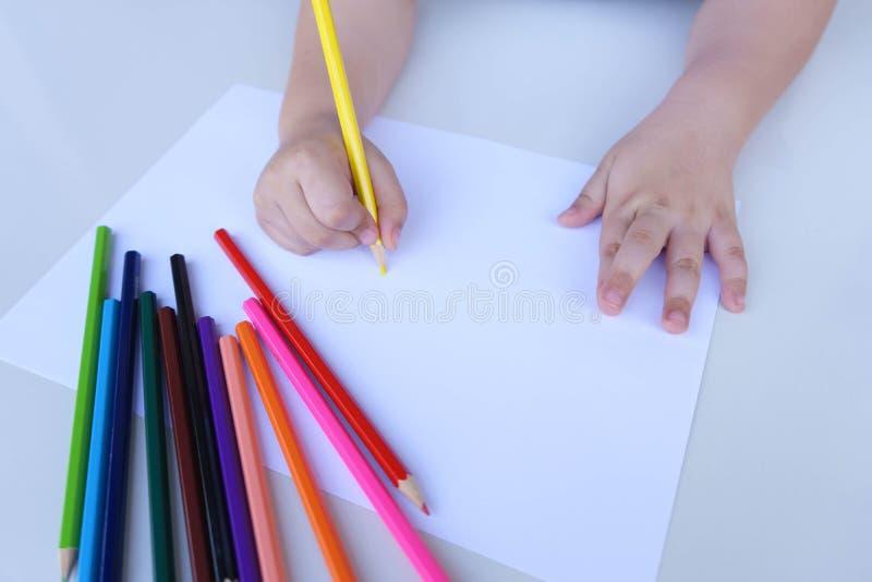 Το χέρι του παιδιού που προετοιμάζεται να γράψει σε ένα άσπρο φύλλο του εγγράφου με τα χρωματισμένα μολύβια Εκπαίδευση και έννοια στοκ φωτογραφία με δικαίωμα ελεύθερης χρήσης