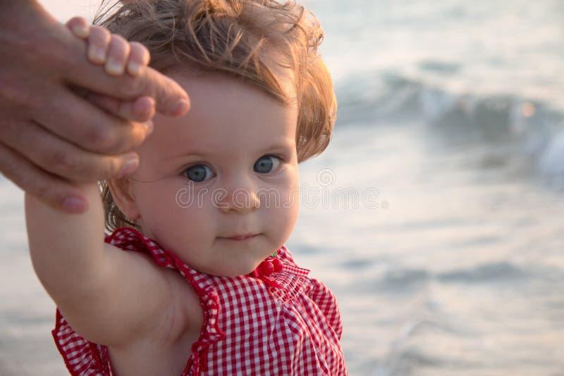 Το χέρι του πατέρα οδηγεί το κορίτσι παιδιών του στη φύση θερινών παραλιών υπαίθρια, την εμπιστοσύνη και μαζί την οικογενειακή έν στοκ φωτογραφία με δικαίωμα ελεύθερης χρήσης