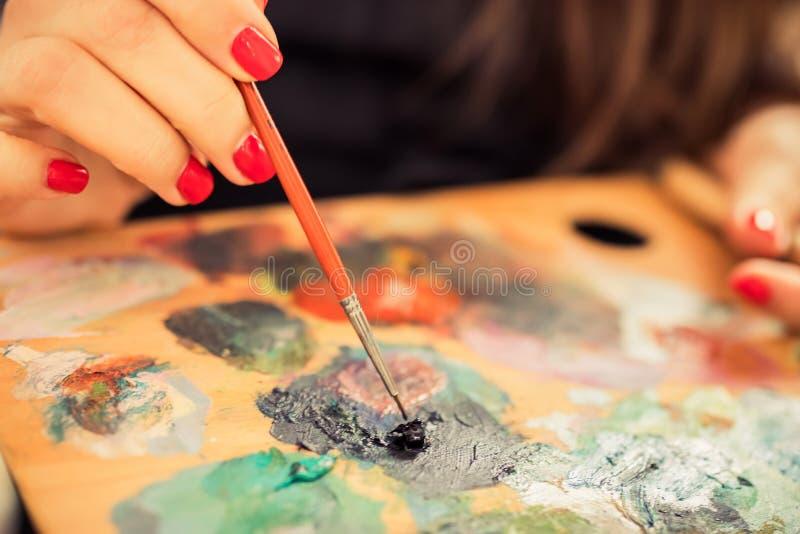 Το χέρι των γυναικών του καλλιτέχνη με ένα πινέλο και μια παλέτα με μπογιές λαδιού Χρωματισμός με λάδι μεικτού χρωματισμού καλλιτ στοκ εικόνα με δικαίωμα ελεύθερης χρήσης