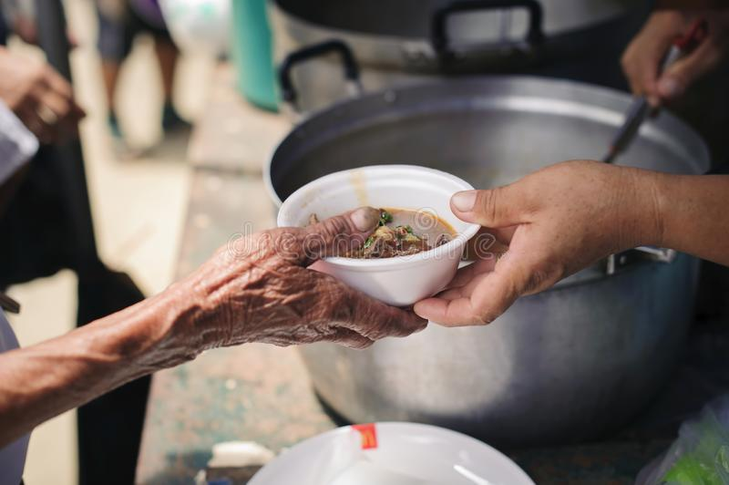Το χέρι των επαιτών λαμβάνει τα τρόφιμα φιλανθρωπίας από τα συντροφικά ανθρώπινα οντα: Η έννοια του ανθρωπισμού: Τα χέρια των προ στοκ φωτογραφία με δικαίωμα ελεύθερης χρήσης