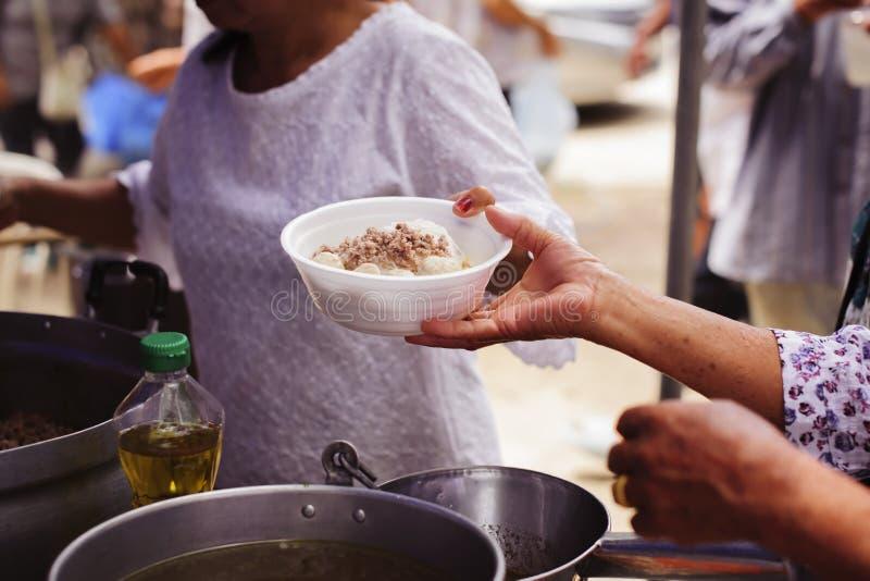 Το χέρι των επαιτών λαμβάνει τα τρόφιμα φιλανθρωπίας από τα συντροφικά ανθρώπινα οντα: Η έννοια του ανθρωπισμού: Τα χέρια των προ στοκ φωτογραφία