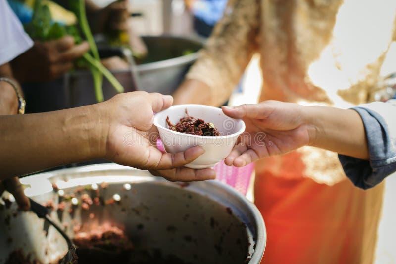 Το χέρι των επαιτών λαμβάνει τα τρόφιμα φιλανθρωπίας από τα συντροφικά ανθρώπινα οντα: Η έννοια του ανθρωπισμού: Τα χέρια των προ στοκ εικόνα με δικαίωμα ελεύθερης χρήσης