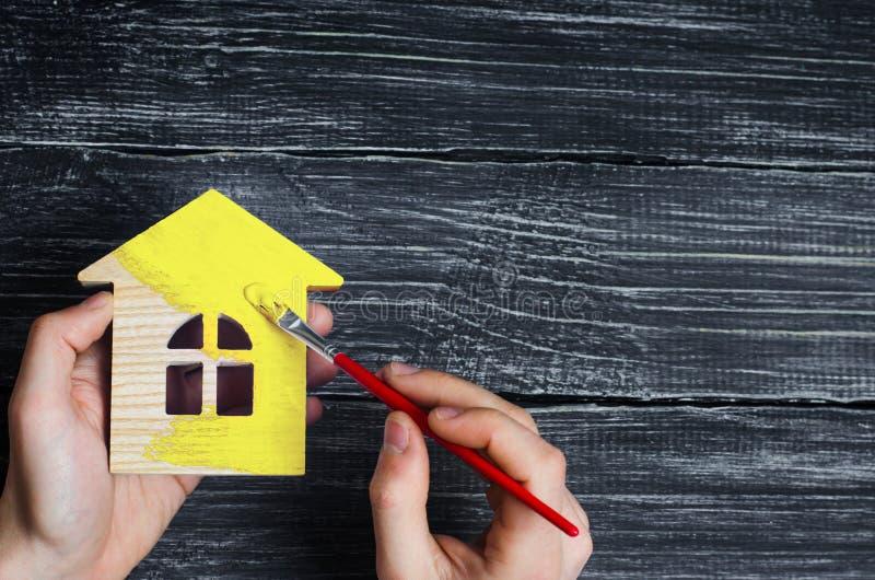 Το χέρι χρωματίζει ένα σπίτι μέσα στο κίτρινο χρώμα Έννοια της επισκευής, χόμπι, εργασία Επισκευή και ζωγραφική των ξύλινων ειδωλ στοκ φωτογραφία