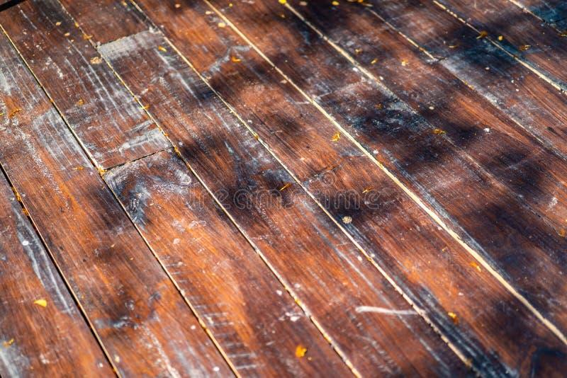 Το χαλασμένο υπαίθριο ξύλινο πιάτο τακτοποιεί και μετασχηματίζει στο πάτωμα με τη σκιά του δέντρου στοκ φωτογραφίες
