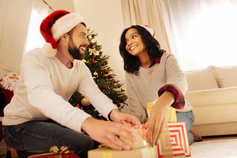Το χαμογελώντας άτομο που βοηθά τη σύζυγό του που τίθεται παρουσιάζει κάτω από το χριστουγεννιάτικο δέντρο στοκ εικόνες με δικαίωμα ελεύθερης χρήσης