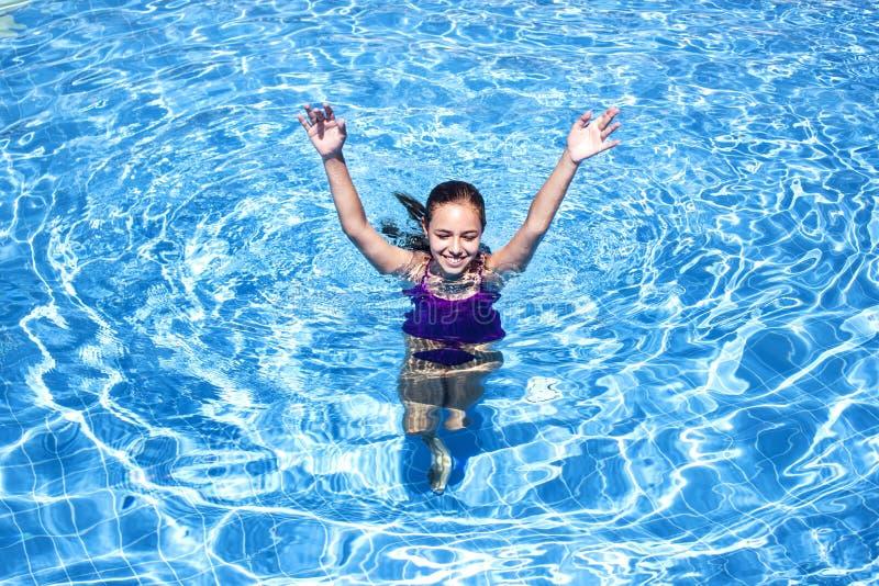 Το χαμογελώντας έφηβη κολυμπά στην υπαίθρια λίμνη στοκ εικόνες