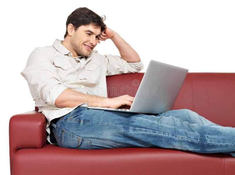 Το χαμογελώντας ευτυχές άτομο με το lap-top κάθεται στο ντιβάνι στοκ εικόνα