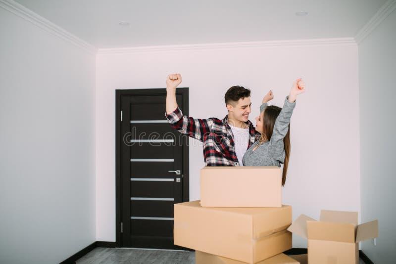 Το χαμογελώντας ζεύγος με παραδίδει το νέο σπίτι μετά από να κινηθεί στοκ εικόνα
