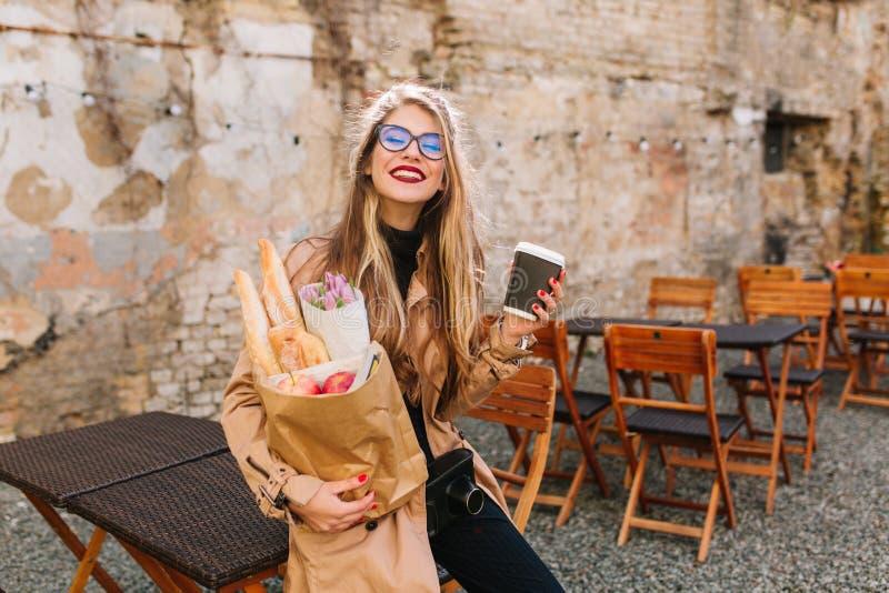 Το χαμογελώντας κορίτσι αγόρασε τα αγαπημένα κουλούρια της στο αρτοποιείο και πίνει τον καφέ που ικανοποίησε με τις αγορές Ελκυστ στοκ φωτογραφία με δικαίωμα ελεύθερης χρήσης