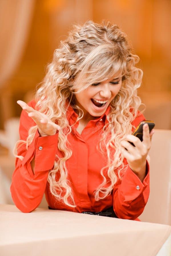 Το χαμογελώντας κορίτσι δακτυλογραφεί το κείμενο στο τηλέφωνο στοκ φωτογραφία με δικαίωμα ελεύθερης χρήσης