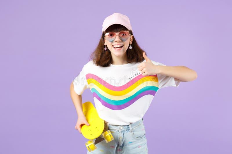 Το χαμογελώντας κορίτσι εφήβων στα ζωηρά ενδύματα, eyeglasses καρδιών κρατά κίτρινο skateboard, που παρουσιάζει αντίχειρα που απο στοκ φωτογραφία με δικαίωμα ελεύθερης χρήσης