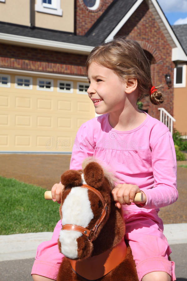 Το χαμογελώντας κορίτσι οδηγά στο άλογο παιχνιδιών κοντά στο εξοχικό σπίτι στοκ εικόνες