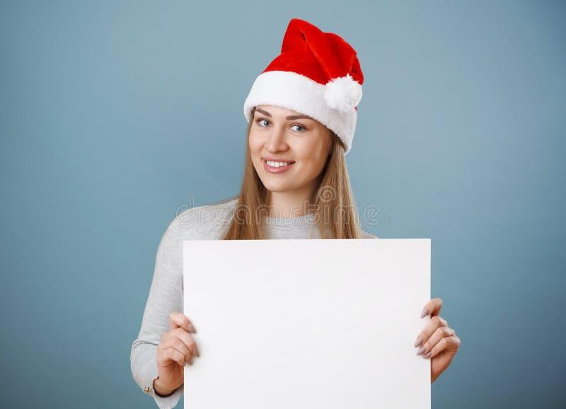 Το χαμογελώντας κορίτσι Χριστουγέννων κρατά τη μεγάλη άσπρη κάρτα Καπέλο Santa στοκ φωτογραφία με δικαίωμα ελεύθερης χρήσης