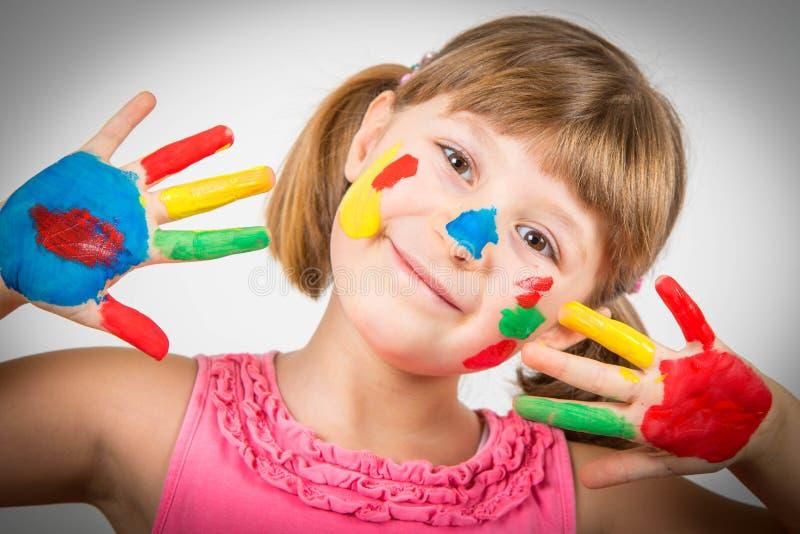 Το χαμογελώντας μικρό κορίτσι με τα χέρια χρωμάτισε στα ζωηρόχρωμα χρώματα στοκ φωτογραφία