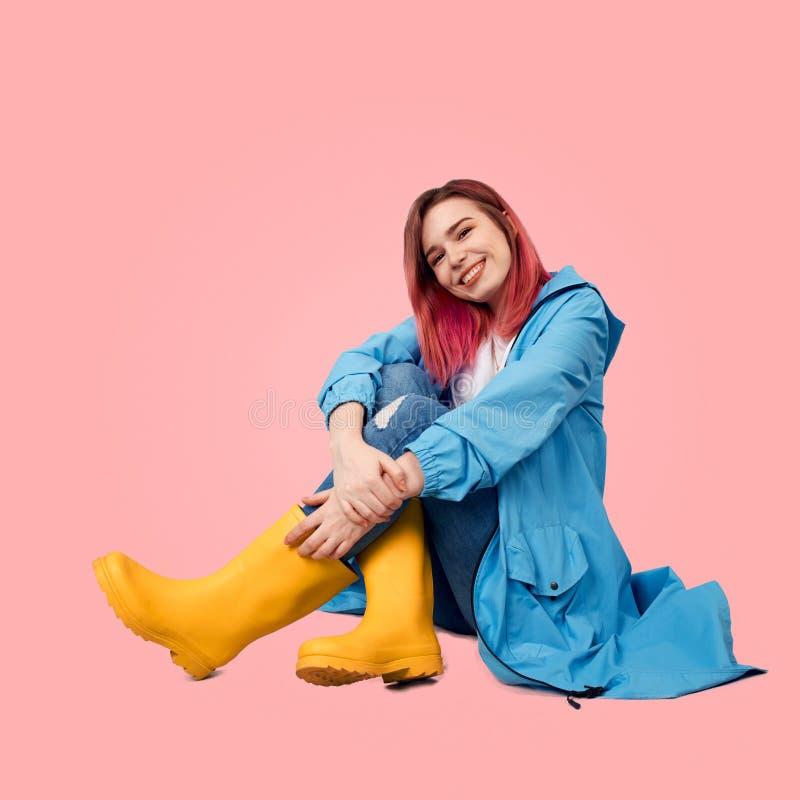 Το χαμογελώντας νέο κορίτσι κάθεται στο πάτωμα που φορά το αδιάβροχο άνοιξη που προστατεύεται από τη βροχή και τις ψηλές κίτρινες στοκ εικόνες με δικαίωμα ελεύθερης χρήσης