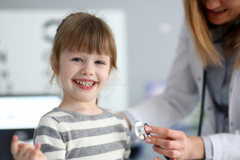 Το χαμογελώντας χαριτωμένο μικρό κορίτσι με το γιατρό που μετρά την καρδιά κτύπησε με το στηθοσκόπιο στοκ εικόνα με δικαίωμα ελεύθερης χρήσης