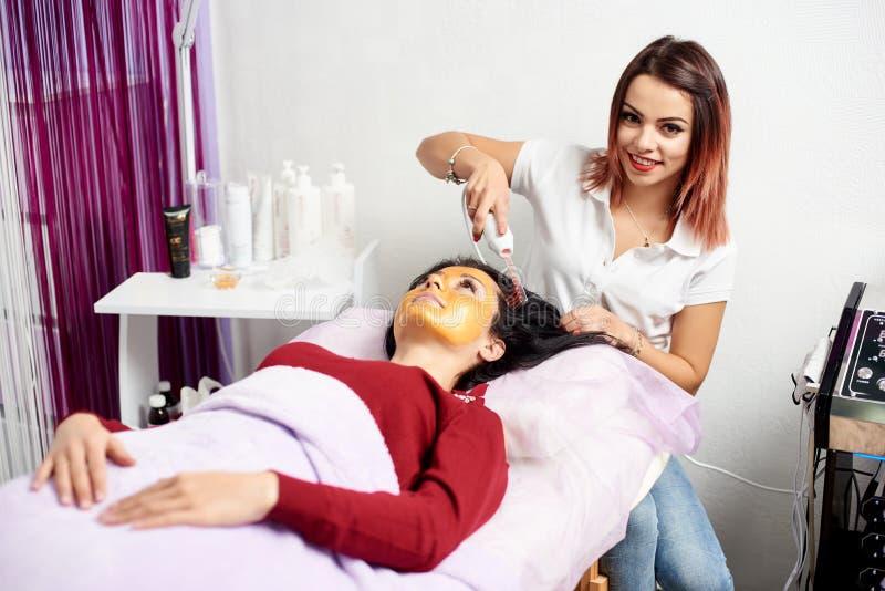Το χαμογελώντας cosmetologist κάνει τη διαδικασία τη microcurrent θεραπεία στην τρίχα όμορφου στοκ φωτογραφίες με δικαίωμα ελεύθερης χρήσης