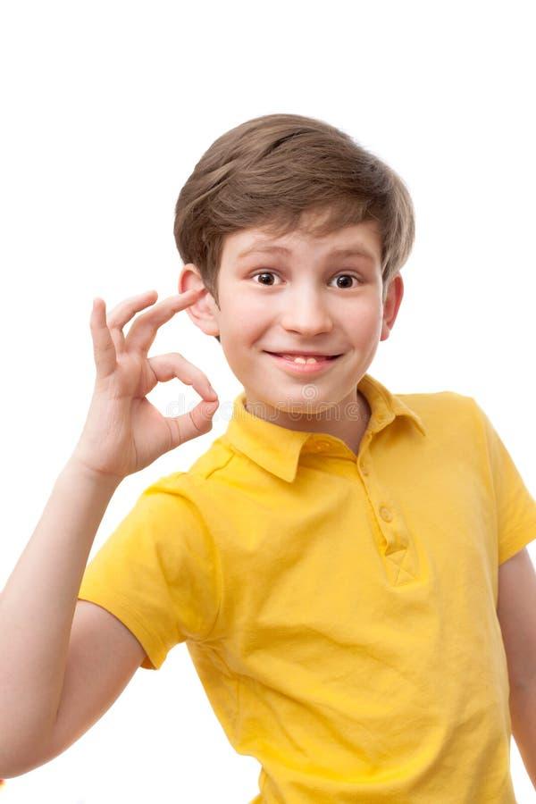 Το χαμογελώντας αγόρι στην κίτρινη μπλούζα παρουσιάζει μια χειρονομία εντάξει στοκ εικόνες με δικαίωμα ελεύθερης χρήσης
