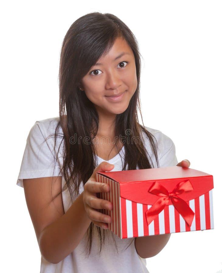 Το χαμογελώντας ασιατικό κορίτσι έχει ένα παρόν στοκ φωτογραφίες με δικαίωμα ελεύθερης χρήσης